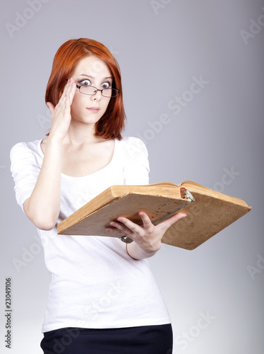 Red-haired businesswoman keep book in hand.