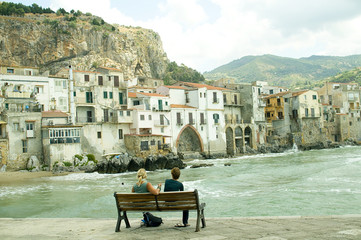 Couple sitting on a bench near the ocean in Cefalu, Sicily