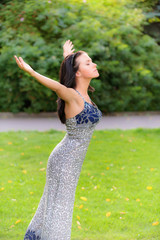 Girl stands on lawn and lifts upwards hands