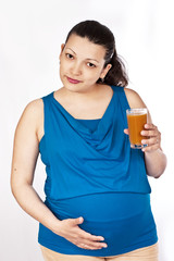 pregnant girl holds glass of apricot juice