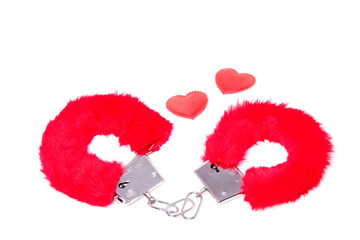to sexy red handcuffs with two hearts isolated over white