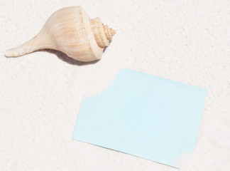 Blank note on beach by shell