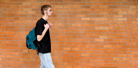 Student walking besides brick wall