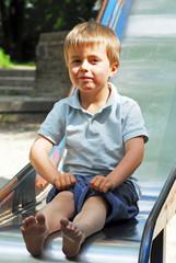 Frecher Junge auf einer Rutsche