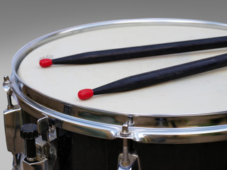 Snare drum and two black sticks with red tips