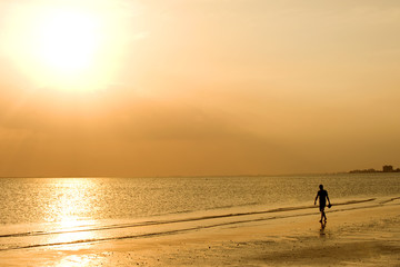 Man strolling along the waves at Fort Myers Beach, Florida
