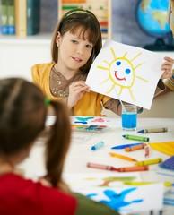 Schoolgirl showing painting in art class