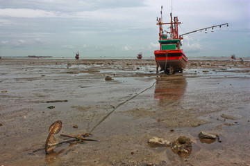 Fishing boat stuck on shore with an anchor