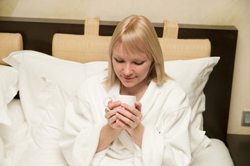 Woman drinking a tea sitting on her bed