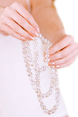 girl holding white pearl beads