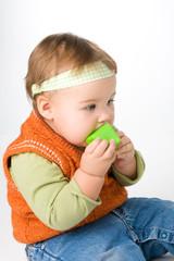The little girl chews  block