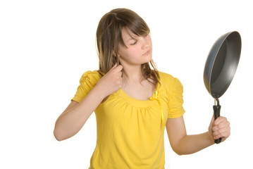Girl looks in reflexion at bottom of frying pan
