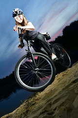 Portrait of a  girl on a bicycle in summer lake outdoors