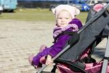 copilul stand intr-un carucior la plimbare
