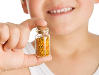 Little boy holding small bottle of pollen - closeup