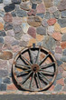 Old wagon wood wheel against an house wall