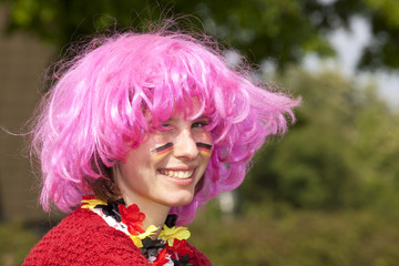 lächelnder weiblicher Fussballfan mit Perücke