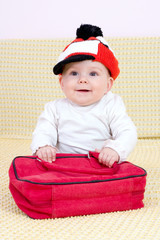 Kid in red hat and bag