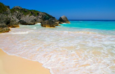 Sandy beach and rocky coastline with blue ocean water (Bermuda)