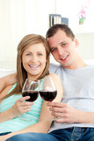 Portrait of a happy young couple drinking red wine
