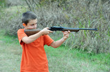 Boy firing rifle