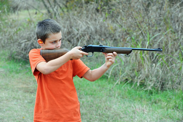 Boy firing rifle