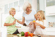Grandchildren Helping Grandmother To Prepare Salad In Kitchen