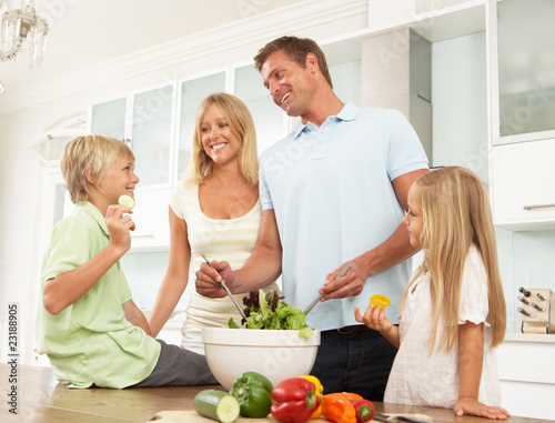 Family Preparing Salad In Modern Kitchen