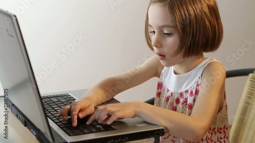 Little girl at work on her laptop.