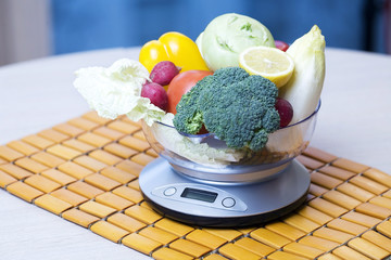 Fresh vegetables with kitchen scales