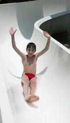 Smiling boy slides a waterslide