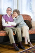 Happy senior couple sitting together on couch