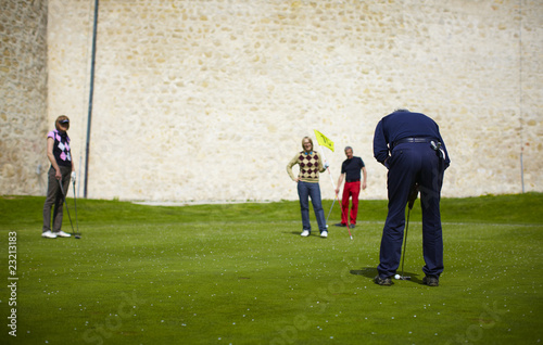 Man putting on the green with group of golfers watching