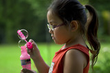 Asian child in ponytail playing outside with bubbles poster