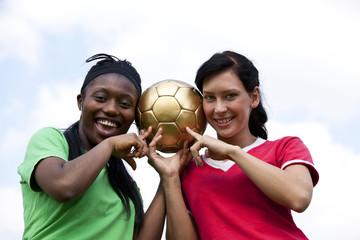 zwei lächelnde Fussballerinnen zeigen auf den Ball