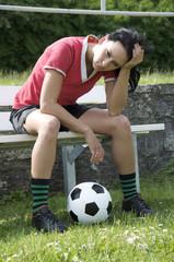 Junge Fussballspielerin auf Reservebank