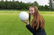 Elegante Frau mit Fussball auf Fussballplatz
