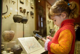 little girl writes to writing-books at excursion in museum