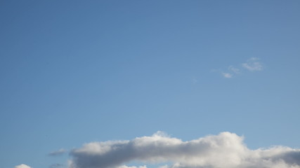 White clouds roll across a blue sky, turning from white to gray