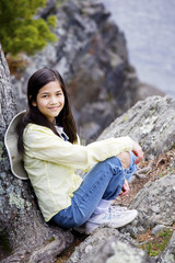 Girl sitting on rock cliff edge