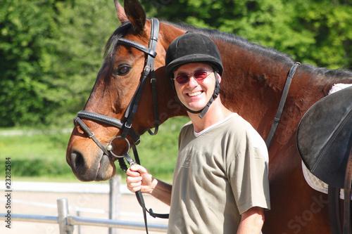 Mann mit Pferd fertig zum Ausritt