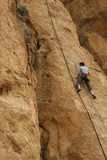 Rock climber works his way up a sheer cliff face