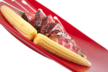 meat served on white with corns