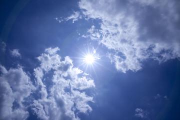 青空に太陽光線で雲が光る