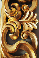 Closeup of golden stucco decoration in curve shape