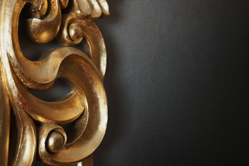 golden stucco decoration in curve shape against dark wall
