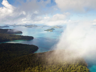Aerial view of the Whitsunday Islands through misty clouds