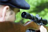 Man looking through scope on a rifle gun poster
