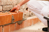bricklayer making wall with brick and grout poster