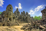 Cambodian temple ruins turning to rubble, blue sky background poster